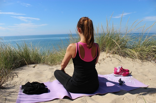 Woman meditating on a yoga mat at the beach